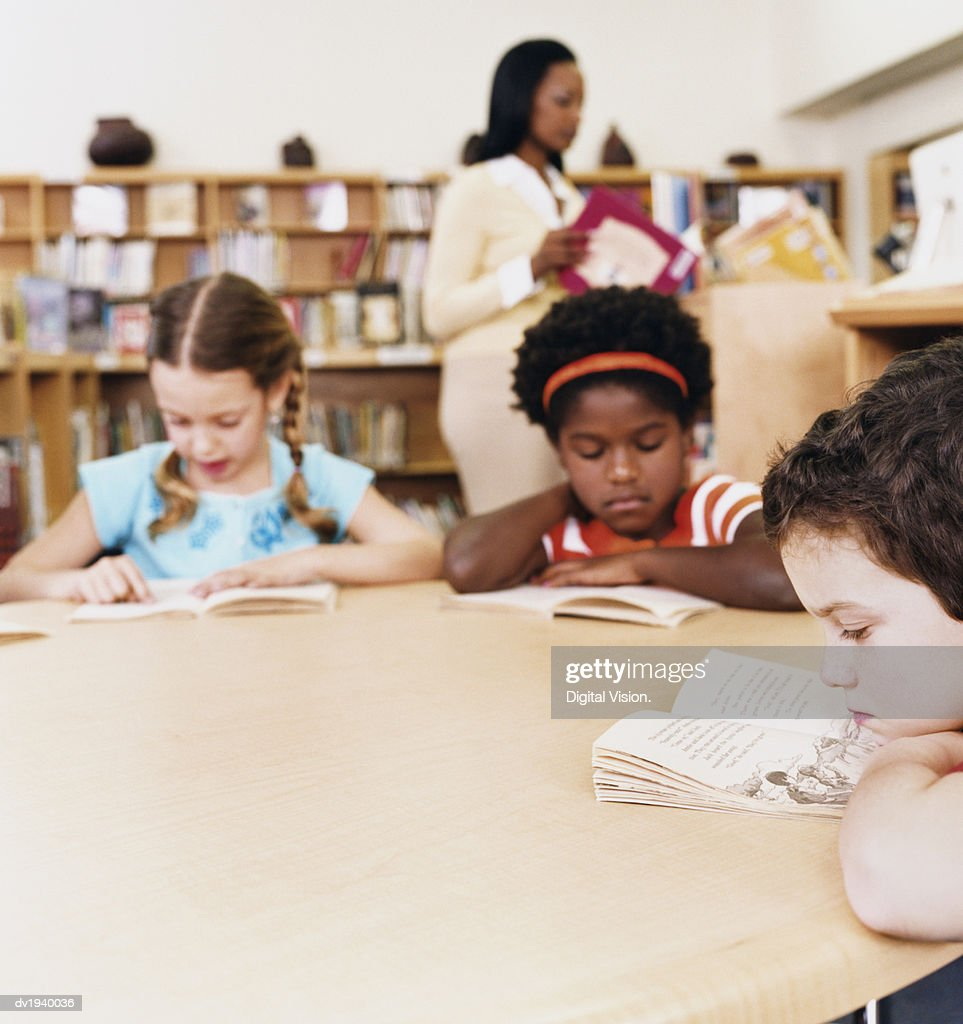 Young Children Reading Books in a Library : Stock Photo