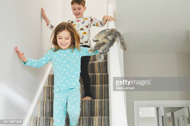 young children running downstairs - pyjamas stock pictures, royalty-free photos & images