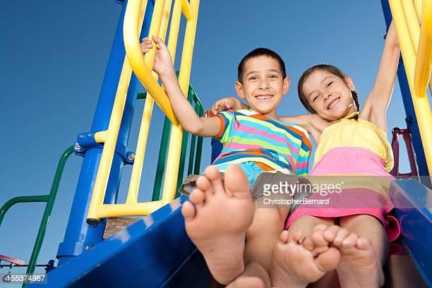 Junge Kinder Rutschen auf der Folie