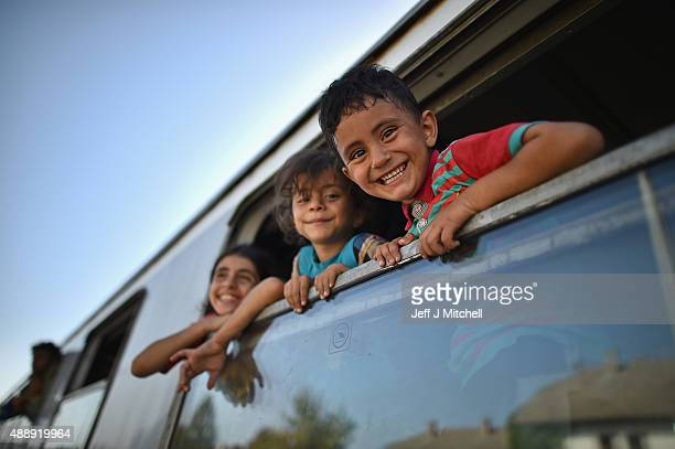 Young children smile a they look out of a train window as migrants board trains and busses at the train station in Beli Manastir near Hungarian...