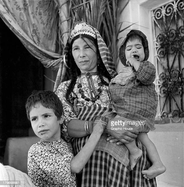 Young children tired of the stifling atmosphere of the synagogue come outside to be with their mother in Djerba Tunisia