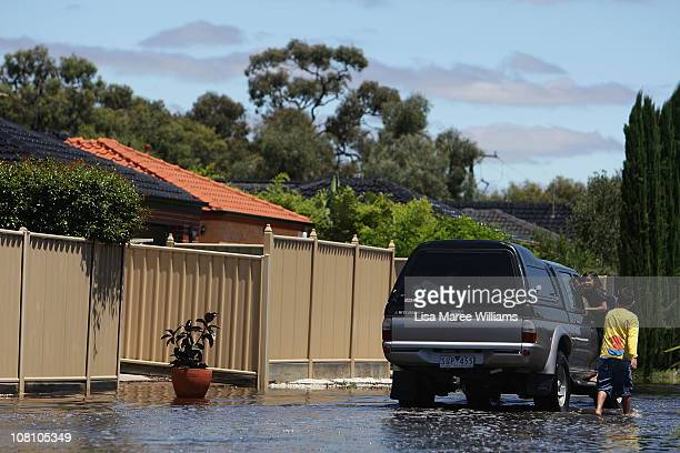 Young children walk alongside a car on a flooded street on January 18 2011 in Horsham Australia Residents and emergency crews sandbagged properties...