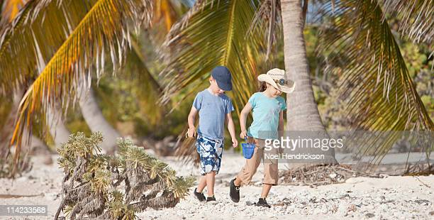 2 young children walk down a beach together