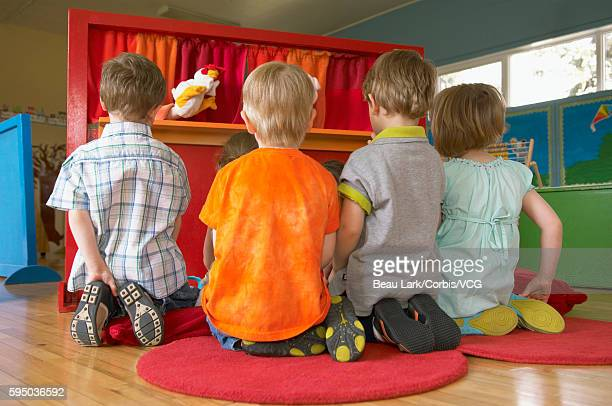 young children watching a puppet show - puppet show stock photos and pictures