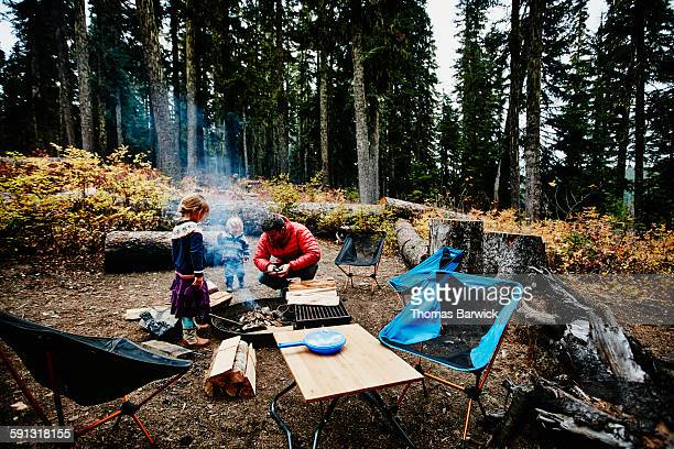 young children watching father start campfire - simple living stock pictures, royalty-free photos & images