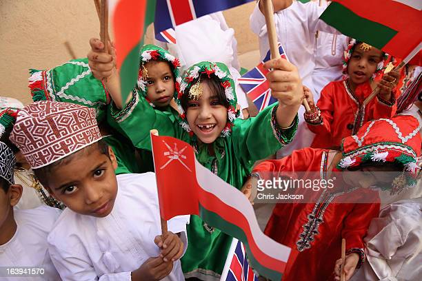 Young children wave flags as Prince Charles Prince of Wales and Camilla Duchess of Cornwall visit Nizwa Fort on the eighth day of a tour of the...