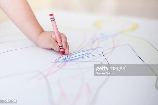 Young child's hand holding a crayon