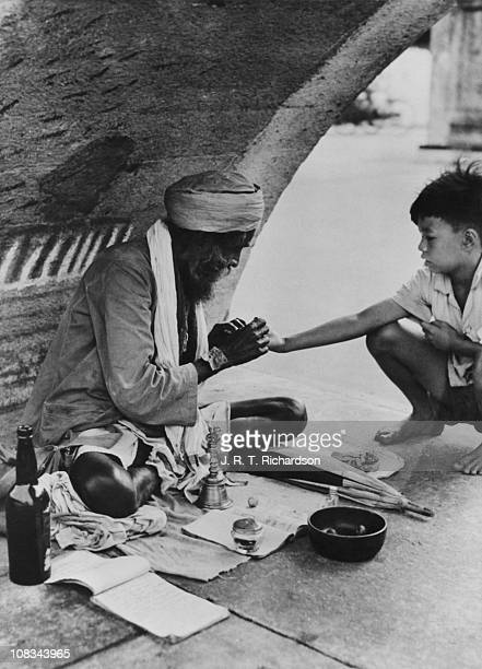 A young Chinese boy has his hand read by an Indian fortuneteller under Elgin Bridge Singapore January 1948
