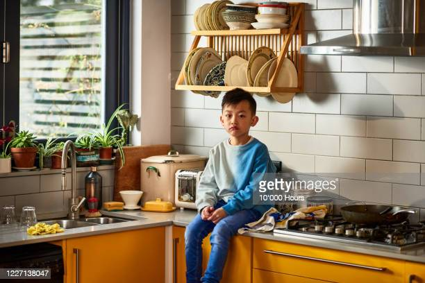 young chinese boy sitting on kitchen counter - east asian ethnicity stock pictures, royalty-free photos & images