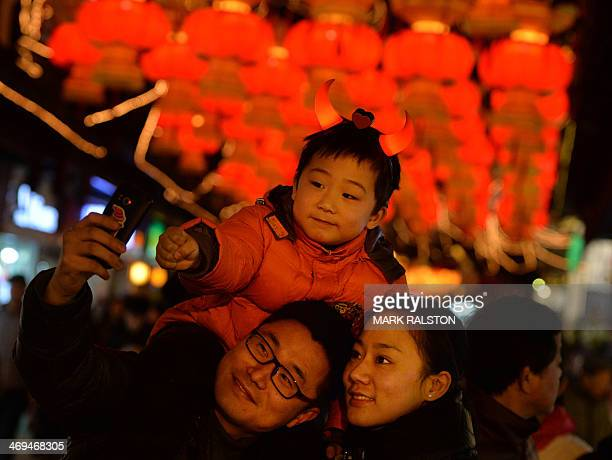 A young Chinese boy wearing horns poses for a photo with his parents as they visit the Lantern Festival decorations in the Yuyuan Gardens of Shanghai...