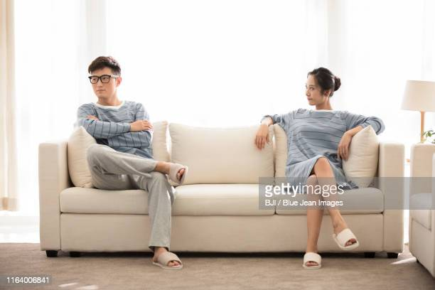 young chinese couple arguing in living room - 足を組む ストックフォトと画像