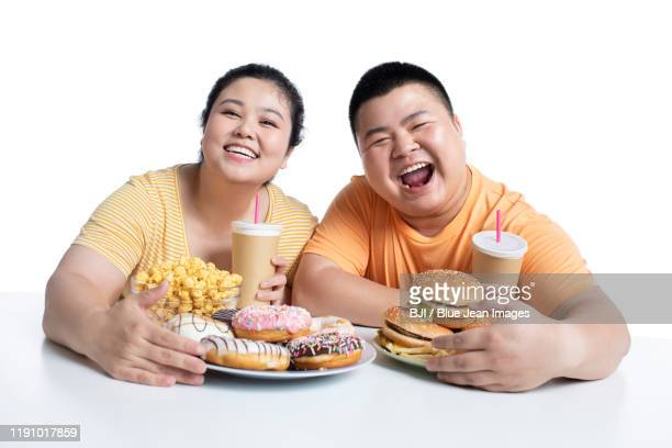 young chinese couple eating fast food - fat people eating donuts stock pictures, royalty-free photos & images