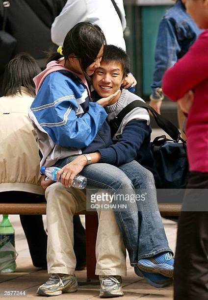 A young Chinese couple hug on a bench as thousands of shoppers gather outside a shopping complex in Beijing 02 October 2003 The National Day holiday...