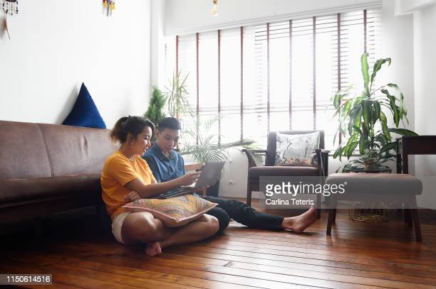 young chinese couple sitting on the floor at home with a laptop - heterosexual couple stock pictures, royalty-free photos & images