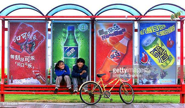 A young Chinese couple take refuge from the rain at a bus stop sponsored by US soda giant Cocacola 27 September 2000 outside one of the company's...