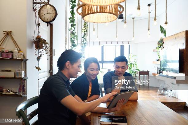 Young Chinese couple with a financial advisor at home