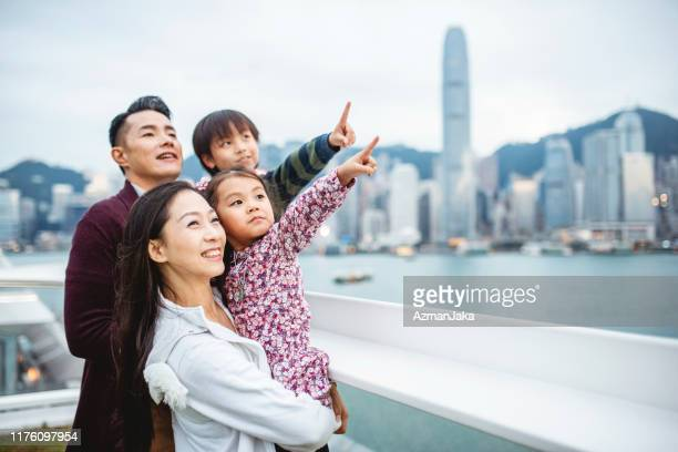 young chinese family pointing to hong views from deck - asia pac stock pictures, royalty-free photos & images