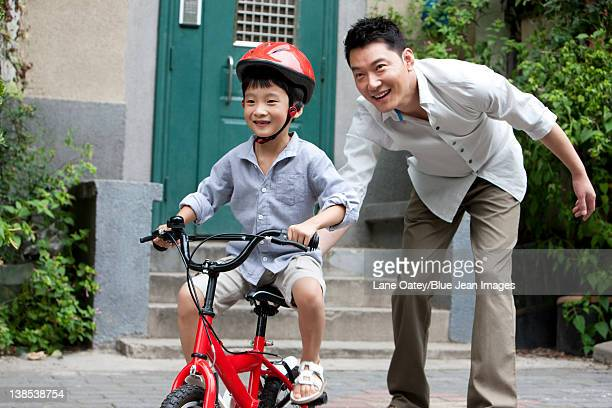 Young Chinese father training son to ride a bike