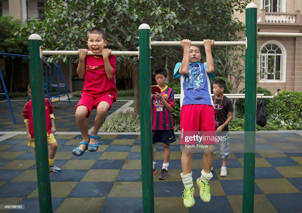 Young Chinese football players exercise on pull-up bars at the Evergrande International Football School on June 12, 2014 near Qingyuan in Guangdong Province, China. The sprawling 167-acre campus is the brainchild of property tycoon Xu Jiayin, whose ambition is to train a generation of young athletes to establish China as a football powerhouse. The school is considered the largest football academy in the world with 2400 students, more than 50 pitches and a squad of Spanish coaches through a partnership with Real Madrid.