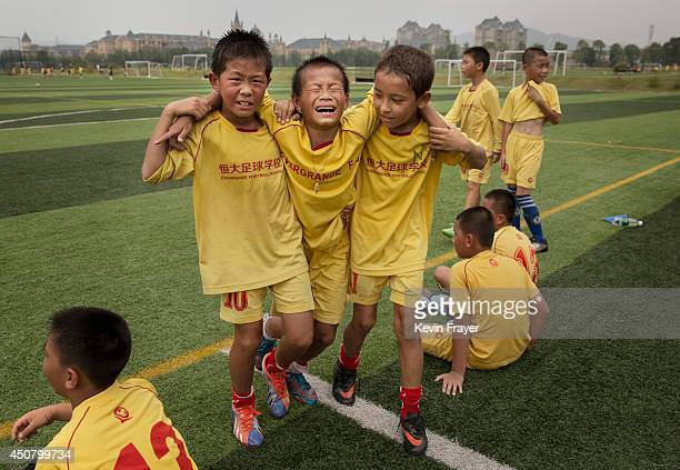 Young Chinese football players help an injured player off the field during training at the Evergrande International Football School on June 12 2014...