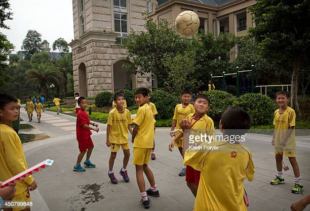 Young Chinese football players play with a ball outside their class at the Evergrande International Football School on June 12 2014 near Qingyuan in...