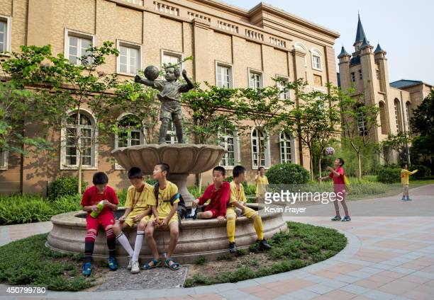 Young Chinese football players sit together in the campus as they wait to head to training at the Evergrande International Football School on June 14...