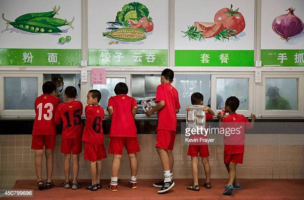 Young Chinese football players wait on line for lunch after training at the Evergrande International Football School on June 13 2014 near Qingyuan in...