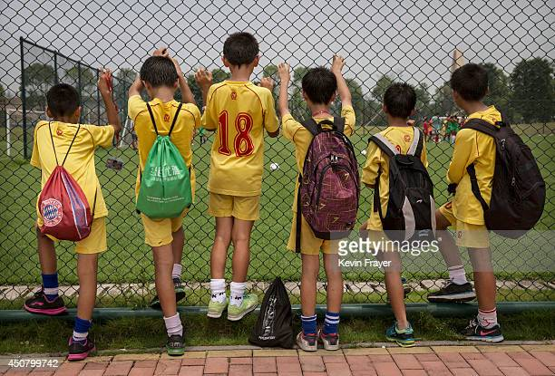 Young Chinese football players watch others training at the Evergrande International Football School on June 12 2014 near Qingyuan in Guangdong...