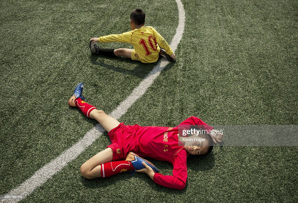 Young Chinese football stretch during training at the Evergrande International Football School on June 13, 2014 near Qingyuan in Guangdong Province, China. The sprawling 167-acre campus is the brainchild of property tycoon Xu Jiayin, whose ambition is to train a generation of young athletes to establish China as a football powerhouse. The school is considered the largest football academy in the world with 2400 students, more than 50 pitches and a squad of Spanish coaches through a partnership with Real Madrid.