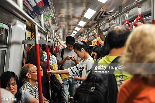 Young chinese girl looking at her smartphone in the train