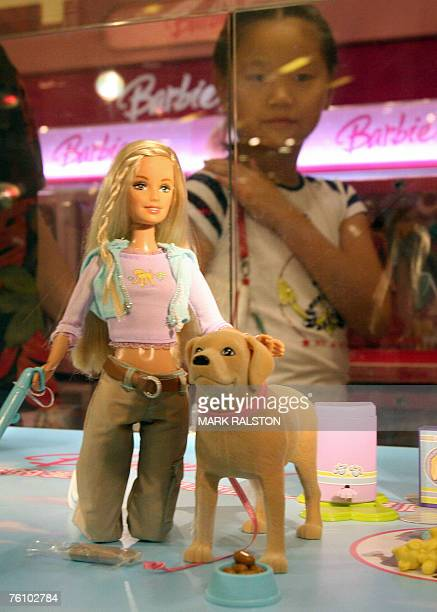 A young Chinese girl looks at a 'Barbie and Tanner' toy made by US toy giant Mattel which is still for sale in China despite being recalled in the US...