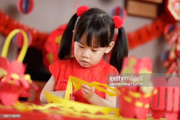 young chinese girl making traditional chinese fu means lucky lantern for celerating chinese new year - flower moon stock pictures, royalty-free photos & images