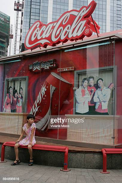 A young Chinese girl rests at the CocaCola music pavillion beneath a giant Coke sign inside the small park of the Xiangyan Fashion Market