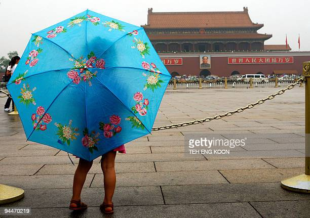 A young Chinese girl uses an umbrella to protect herself from a light rain at Tiananmen Square in Beijing 29 June 2007 Beijing's weather bureau said...