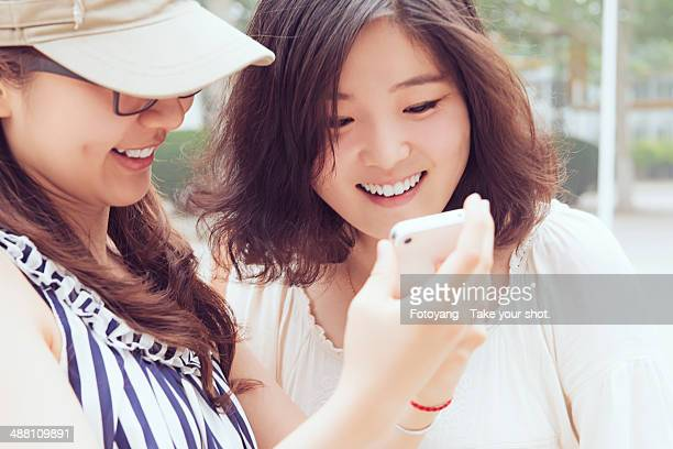 Young Chinese Girls Checking Smartphone.