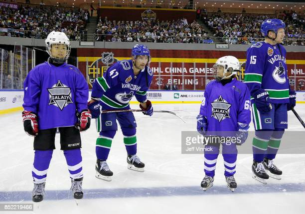 Young Chinese hockey players stand beside Sven Baertschi and Derek Dorsett of the Vancouver Canucks before their preseason game against the Los...