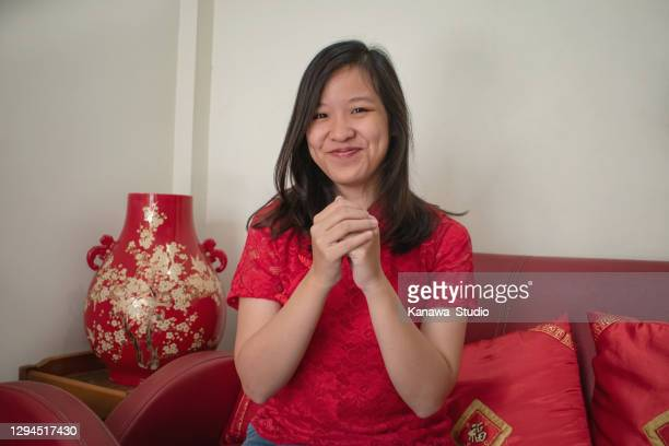 young chinese indonesian woman folding her hands over each other to greeting gongxi to her family - chinese culture stock pictures, royalty-free photos & images