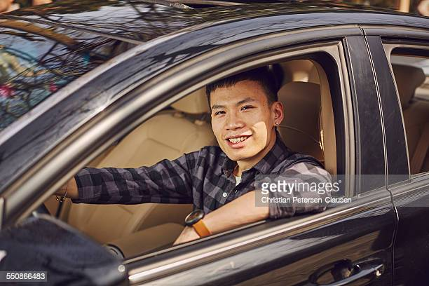 Young Chinese man driving black car smiling