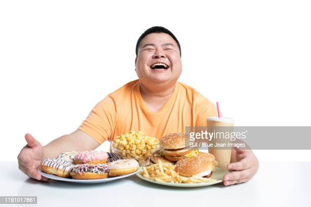 young chinese man eating fast food - fat people eating donuts stock pictures, royalty-free photos & images