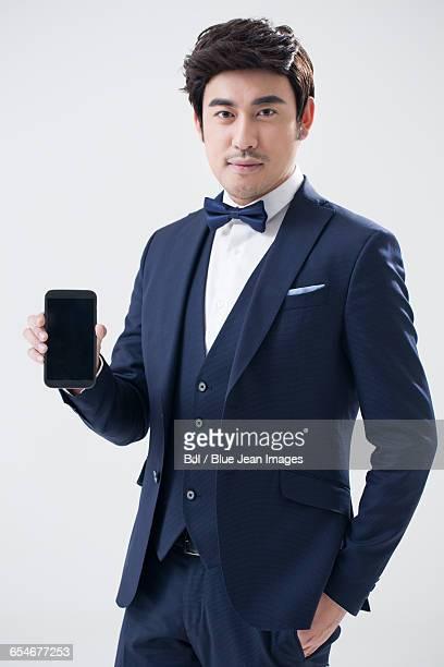 young chinese man showing a smart phone - smoking pak stockfoto's en -beelden