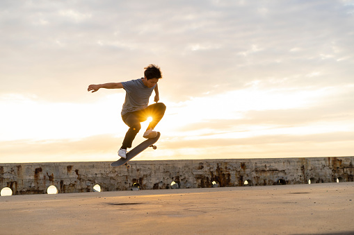 Young Chinese man skateboarding at sunsrise near the beach - gettyimageskorea