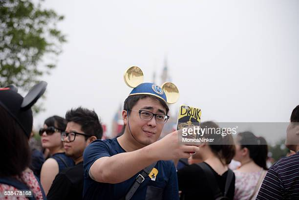 Young chinese man taking a Selfie in Shanghai, Disneyland