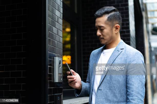 young chinese man using mobile phone unlock door ,smart home