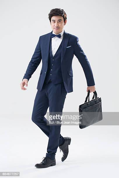 Young Chinese man walking with briefcase