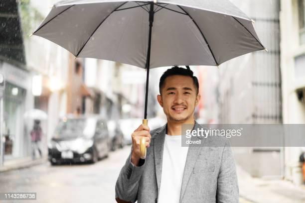 young chinese man with umbrella - 傘 ストックフォトと画像
