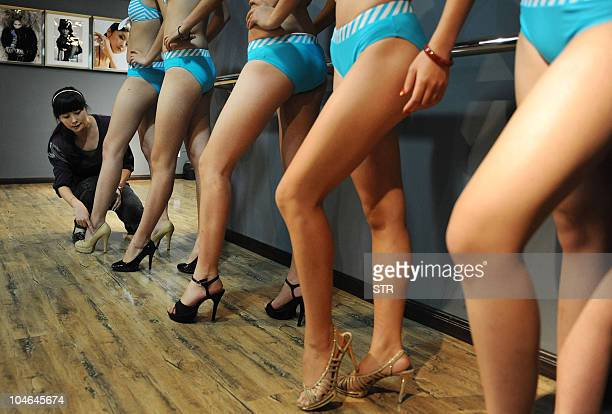 Young Chinese models strike a pose during class at a modelling school in Hefei east China's Anhui province on September 28 2010 Every year hundreds...