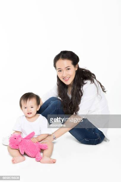 young chinese mom playing with her baby daughter
