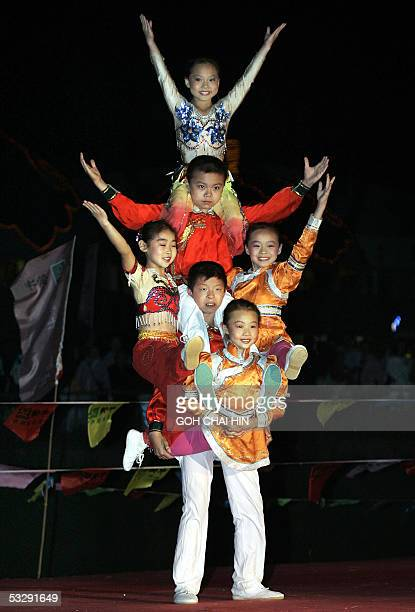 Young Chinese Mongolian acrobats perform during the Naadam festival on the grassland of Gegental Steppe in China's Inner Mongolia region 26 July 2005...