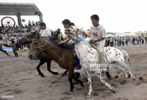 Young Chinese Mongolian horsemen rein in their horses to start a race during the Naadam festival on the grassland of Gegental Steppe in China's Inner...