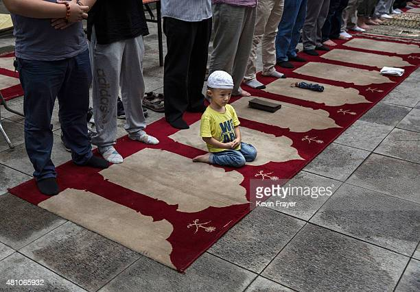 A young Chinese Muslim of the Hui ethnic minority sits on a prayer rug as men stand and pray during the last Friday prayers of the holy fasting month...